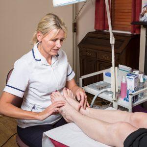 Ann Exton examining a foot